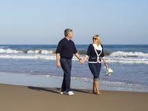 Mogna par för romantiker som promenerar stranden arkivbilder