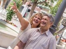 Mogna par för romantiker med kvinnan som pekar ut i ferier Arkivbild