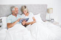 Mogna par genom att använda den digitala minnestavlan i säng Royaltyfria Bilder