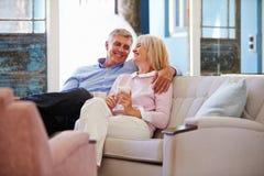 Mogna par hemma som kopplar av i vardagsrum med den varma drinken Fotografering för Bildbyråer