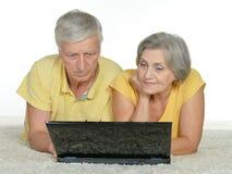 Mogna par med bärbara datorn royaltyfri bild