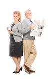 Mogna par med en tidning och en kopp kaffe Fotografering för Bildbyråer