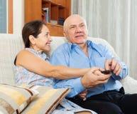 Mogna par med TVfjärrkontrollen Arkivbild