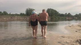 Mogna par - omfamning som förbiser floden Härliga par av pensionärer nära bevattnar Gammalt lyckligt folk som rymmer händer arkivfilmer