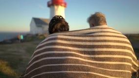 Mogna par som går på solnedgången på kusten med en gammal fyr arkivfilmer