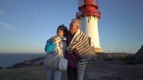 Mogna par som går på solnedgången på kusten med en gammal fyr lager videofilmer