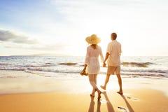 Mogna par som går på stranden på solnedgången arkivbild