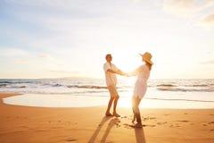 Mogna par som går på stranden på solnedgången royaltyfri fotografi