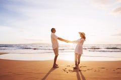 Mogna par som går på stranden på solnedgången arkivfoton