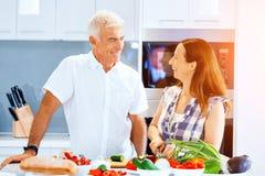 Mogna par som hemma lagar mat arkivfoto