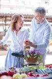 Mogna par som köper nya organiska grönsaker i en marknadsplats för öppen luft royaltyfria foton