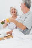 Mogna par som klirrar deras exponeringsglas för orange fruktsaft Arkivfoto