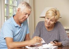 Mogna par som kontrollerar finanser och tillsammans går till och med räkningar Royaltyfri Foto