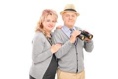 Mogna par som poserar med kikare Royaltyfri Foto