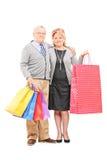 Mogna par som poserar med shoppingpåsar Royaltyfri Foto