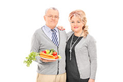 Mogna par som rymmer en platta full av grönsaker Fotografering för Bildbyråer