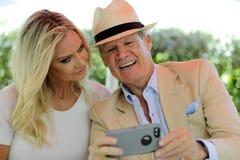 Mogna par som ser foto på en smart mobiltelefon och le royaltyfria foton