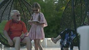 Mogna par som sitter på en hängande stol som tillsammans kopplar av i hotellkomplexet Gullig liten flicka som nära står stock video