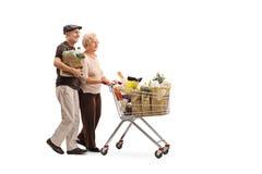 Mogna par som skjuter en shoppingvagn Arkivbild