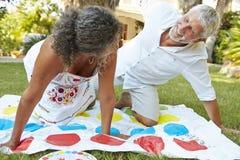 Mogna par som spelar balansera leken i trädgård Royaltyfri Bild