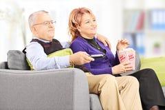Mogna par som äter popcorn och håller ögonen på tv Royaltyfri Foto