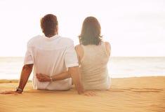 Mogna par som tycker om solnedgång på stranden fotografering för bildbyråer