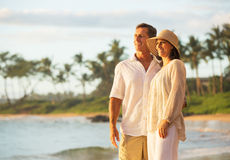 Mogna par som tycker om solnedgång på stranden Arkivbild
