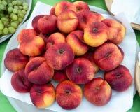 Mogna Peaches Red Yellow Stack på en platta, på försäljning, sikt uppifrån arkivfoto