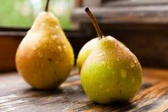 Mogna pears på en trätabell Royaltyfri Foto