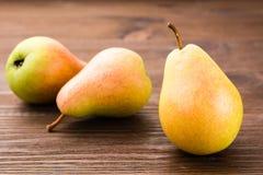 Mogna pears på en trätabell Royaltyfri Bild