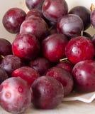 Mogna plommoner och körsbär-plommon på en tabell Royaltyfri Bild