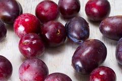 Mogna plommoner och körsbär-plommon på en tabell Arkivfoton