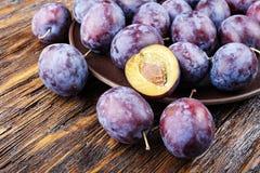 Mogna plommoner på en brun trätabell, sund mat, sommarskörd Royaltyfri Foto