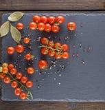 Mogna rå röda körsbärsröda tomater på en svart grafit stiger ombord royaltyfri foto