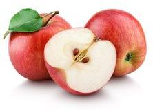 Mogna röda äpplen med halva och äppleblad som isoleras på vit Royaltyfri Bild