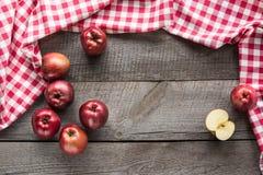 Mogna röda äpplen ombord med den röda rutiga servetten omkring och kopieringsutrymme Fotografering för Bildbyråer