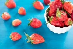 Mogna röda jordgubbar på den blåa trätabellen, ny jordgubbe, jordgubbar i den vita bunken royaltyfri foto