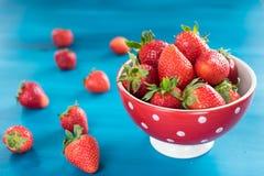 Mogna röda jordgubbar på den blåa trätabellen, ny jordgubbe, jordgubbar i den vita bunken Royaltyfria Foton