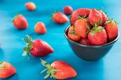 Mogna röda jordgubbar på den blåa trätabellen, ny jordgubbe, jordgubbar i den vita bunken arkivbild