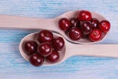 mogna röda körsbär i trätabell för träskednärbildblått Top beskådar arkivfoton