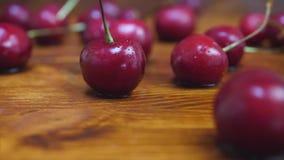 Mogna röda körsbärnedgångar på trätabellen med vattendroppar stock video