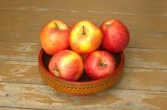 Mogna röda och gula äpplen i träbunkecloseup Royaltyfri Foto