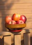 Mogna röda och gula äpplen i träbunkecloseup Arkivbilder