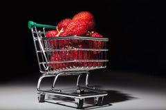 Mogna röda jordgubbar i miniatyrsupermarketspårvagn Royaltyfri Foto
