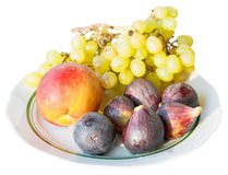 Mogna säsongsbetonade frukter på plattan som isoleras på vit Arkivfoton
