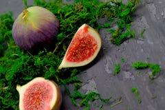 Mogna söta fikonträd, frukt med halva och fjärdedel på mörk bakgrund Arkivbilder