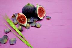 Mogna söta fikonträd, frukt med halva och fjärdedel på rosa bakgrund Royaltyfri Bild