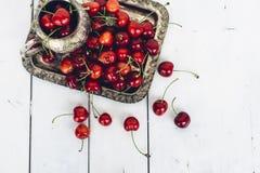 Mogna söta körsbär på silvermagasinet på den målade trätabellen Arkivbilder