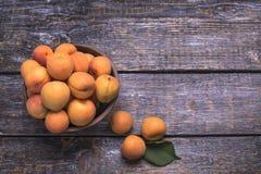 Mogna saftiga aprikors i en korg på en träbakgrund Fotografering för Bildbyråer