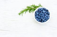 Mogna saftiga blåbärbär i en vit kopp på en vit tabell kopiera avstånd Fotografering för Bildbyråer
